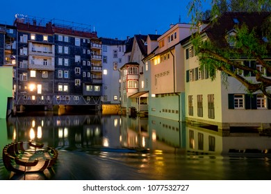 Night shot of the historic quarter Small Venice in Esslingen with the Neckar river and an old wreck in the foreground.