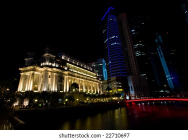 Night shot of hotels and tall buildings along the Singapore river brightly lit