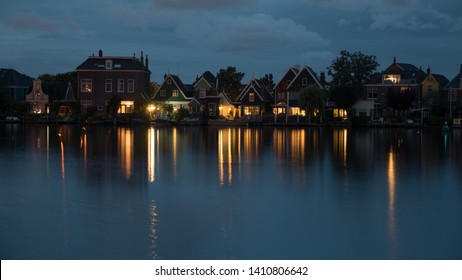 Night shot of houses in Dutch village on riverbank. Lights reflecting on water surface