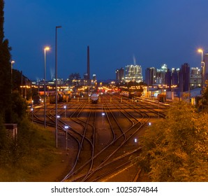 Night shot of an industrial railroad yard with several trains, a refinery in the background.