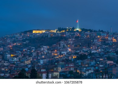 Night shot of Izmir, Turkey cityscape aerial view with illuminated buildings and residences on the hillside