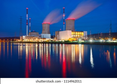 Night shot of a large nuclear power plant close to a river with blue night sky. Tihange, Belgium.