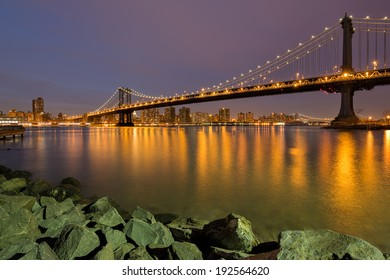 Night shot of the Manhattan Bridge in New York, USA, with beautiful pink skies and yellow lights reflected in Hudson river