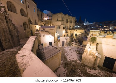 Night shot of Matera, Basilicata, Italy: picturesque ancient streets in the old town called Sassi di Matera in snow, winter