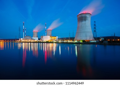 Night shot of a nuclear power plant close at a river with blue night sky.