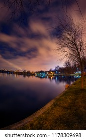 Night shot in the park by the lake with reflections with city lights and a power plant in the background producing thermal energy and steams and a tree in the foreground