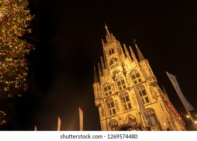 Night shot of part of the old fairylike town hall of Gouda, The Netherlands, with a lot of little windows and towers. On the left a huge decorated Christmas tree.