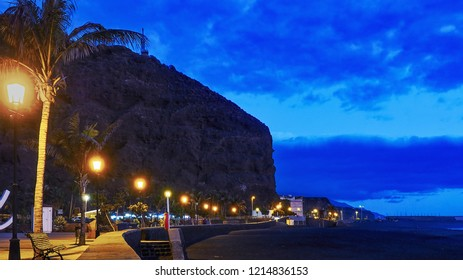 """Night shot of the resort """"Puerto Tazacorte"""" on La Palma, a Canary Island. One sees the promenade with the street lamps and in the background the steep wall of the barranco de Angostinos"""