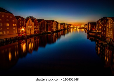 Night shot from the river promenade in the city of Trondheim in Norway - showing a number of the historic buildings along the riverside in beautiful light