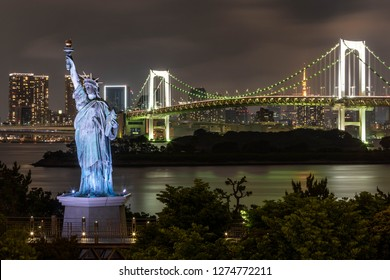 Night shot of Tokyo skyline from Odaiba including the Statue of Liberty replica and the Rainbow Bridge