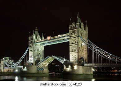a night shot of tower bridge with the bridge raised