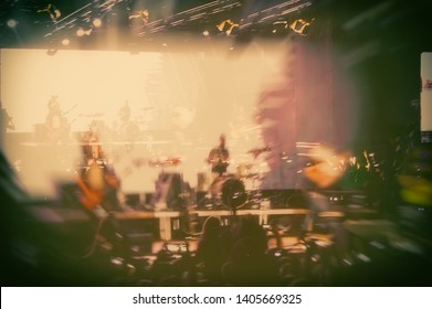 night show with the participation of a rock music band in the open air, blurred background.
