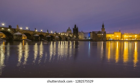 The night side view of famous Charles Bridge in Prague with reflection at Vltava river captured from Vltava river bank during the morning sunrise. Prague, Czech Republic.