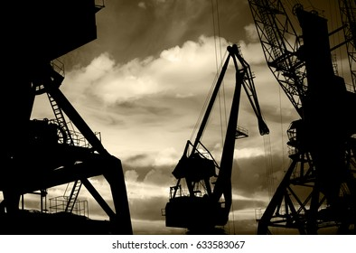Night silhouettes of cargo cranes in the sea port (black & white photo)