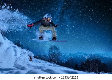 night skating girl is jumping with snowboard from the hill under the starry sky and moonlight