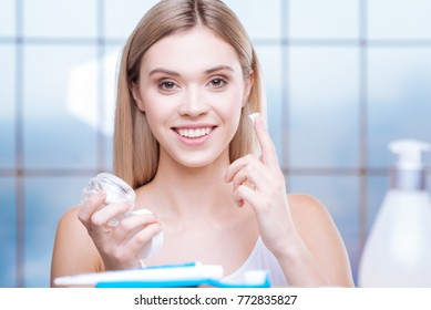 Night skincare routine. Beautiful cheerful young woman being about to apply facial cream to her cheek before going to sleep while smiling at the camera