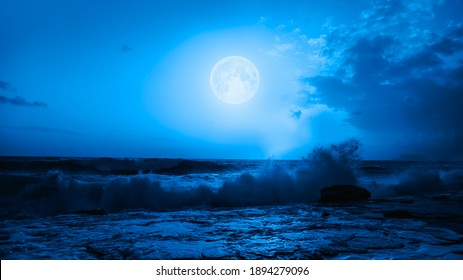 """Night sky with blue moon in the clouds """"Elements of this image furnished by NASA"""