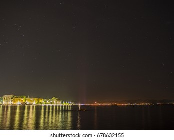 The night sky and the city on the sea in the background