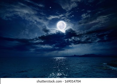 Night sky with full moon and reflection in sea, beautiful clouds. Elements of this image furnished by NASA