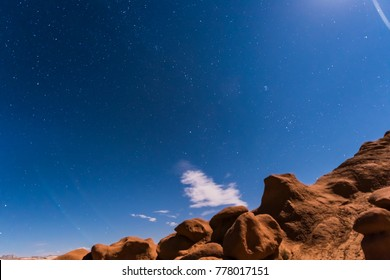 Night sky with full moon rising, or moonrise, in Goblin Valley State Park in Utah showing clouds, stars, and canyons silhouettes in wilderness nature