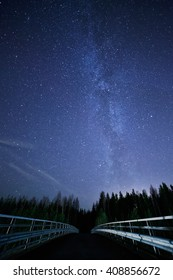 A night sky full of stars and visible milky way with a bridge on foreground. Road leading to dark forest.