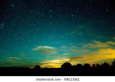 Night sky landscape. Night stars, sky, clouds and meteorite over the fores. Long exposure photography