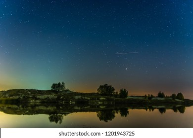 Night sky landscape with stars, over the forest. Long exposure photography.