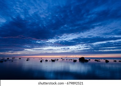 Night sky with large stones above the sea