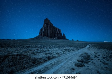 Night sky with many stars above Shiprock and a dirt road. Shiprock is a great volcanic rock mountain rising high above the high-desert plain of the Navajo Nation in New Mexico, USA