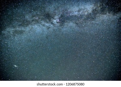 Night sky with the Milky Way galaxy and Andromeda galaxy bottom left amongst countless stars. Constellations swan (Cygnus), Cepheus and Pegasus can be seen.