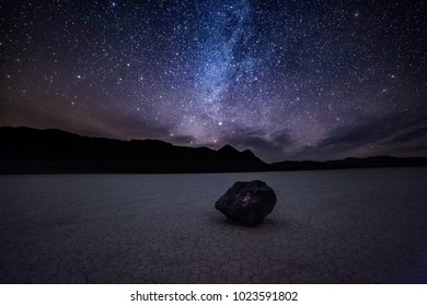 Night sky and the milky way over a moving rock at the Racetrack in Death Valley National Park in California