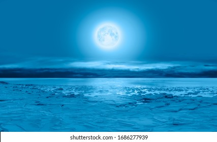 "Night sky with moon in the clouds - Ice on the ocean shore at night ""Elements of this image furnished by NASA"""