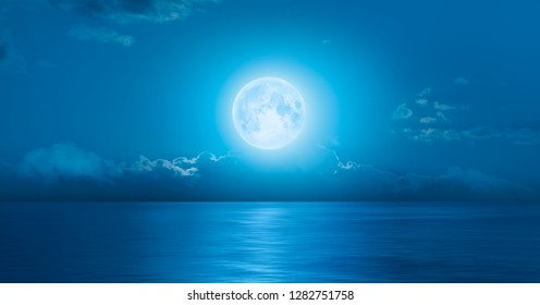 """Night sky with moon in the clouds, on the foreground calm blue sea """"Elements of this image furnished by NASA"""