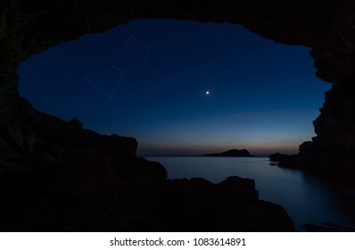Night sky with the moon  venus , orion and sirius at dawn with natural frame , Cala Conta , Ibiza .