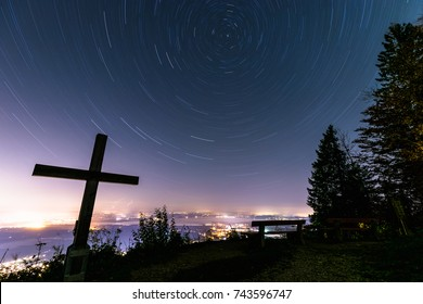 Night sky rotating over lake Chiemsee, with cross and bench, long time exposure, view from Schnappenkirche