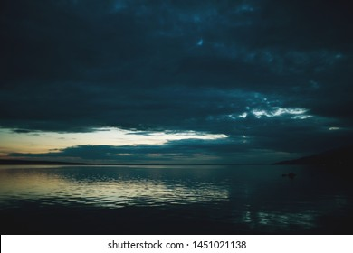 Night sky and sea. The setting sun and calm water. Sunset sky with clouds. Dark ocean water.