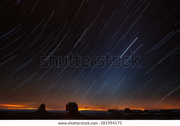 Night sky with star trail above Monument Valley