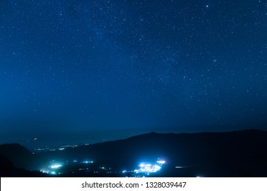 Night sky with stars, city lights in the valley