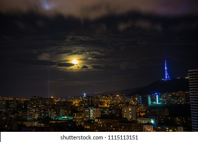 Night sky with stars and moon over new centre of Tbilisi city, Georgia