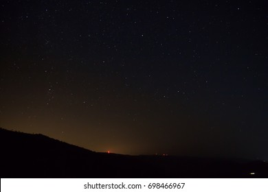Night Sky stars with a red light tint in the horizon, in Ermioni area, Greece