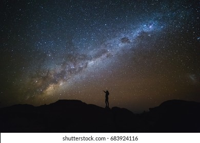 Night sky with stars and silhouette of a standing woman on the mountain. Landscape with Milky Way.