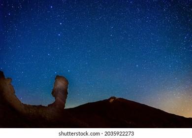 Le ciel nocturne et le volcan du Teide en arrière-plan. Le rocher Roques de Garcia au premier plan. Tenerife, îles Canaries. Espagne.