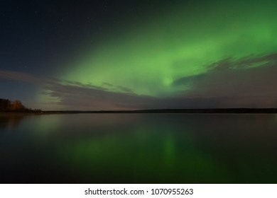 Night sky view of beautiful green aurora borealis, northern polar lights in southern Finland and clouds from below with reflection on the lake shore during geomagnetic storm. Rare phenomenon of nature