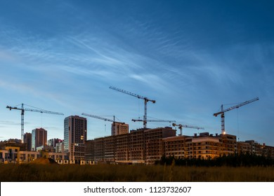 Night sky view of beautiful noctilucent clouds over the city. Cityscape of house building with construsction cranes. Rare phenomena which happens only on summer nights. Cityline with cloudy sky