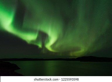 Night sky view of beautiful shape of green aurora borealis, northern polar lights in Norway with reflection on lake shore during geomagnetic storm. Awesome phenomenon of nature near Barents sea.