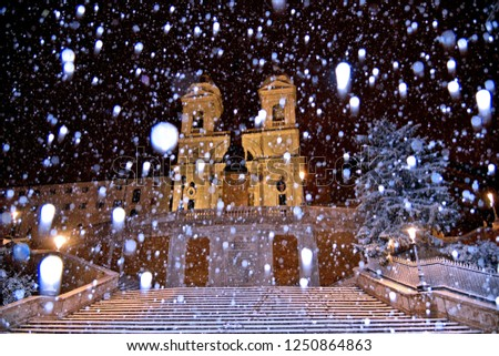 Night snowfall on empty Spanish square and steps in Rome with church Trinita di Monti in background, Italy. Piazza di Spagna