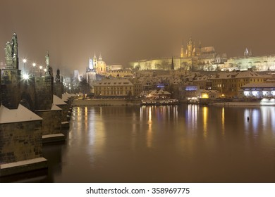 Night snowy Prague gothic Castle and St. Nicholas' Cathedral with Charles Bridge, Czech republic