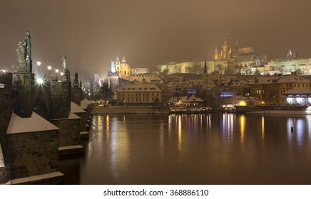 Night snowy Prague Lesser Town with gothic Castle, St. Nicholas' Cathedral and Charles Bridge, Czech republic