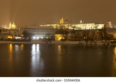 Night snowy Prague Lesser Town with gothic Castle and St. Nicholas' Cathedral above River Vltava, Czech republic