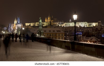 Night snowy Prague Lesser Town with gothic Castle, St. Nicholas' Cathedral from Charles Bridge, Czech republic